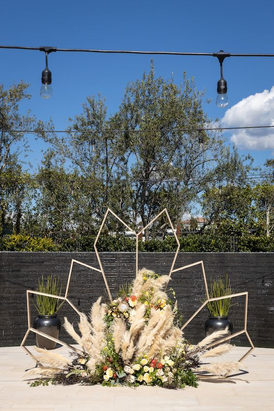 a creative modern wedding backdrop shaped as a leaf of wood, with greenery, pampas grass, bold blooms is a great idea for a mid-century wedding