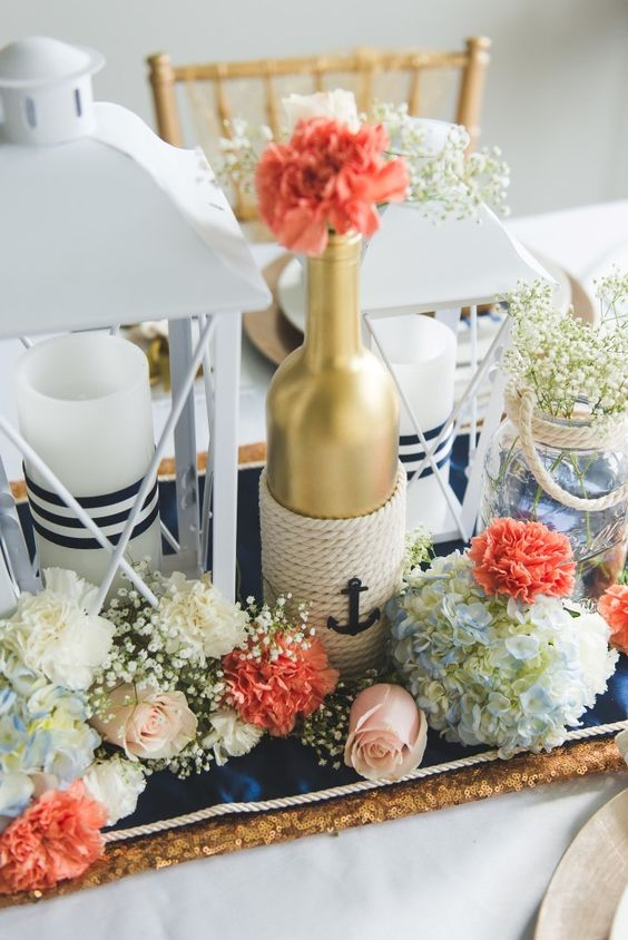 a creative nautical wedding centerpiece of a navy table runner, candle lanterns with stripes, coral and white blooms and baby's breath