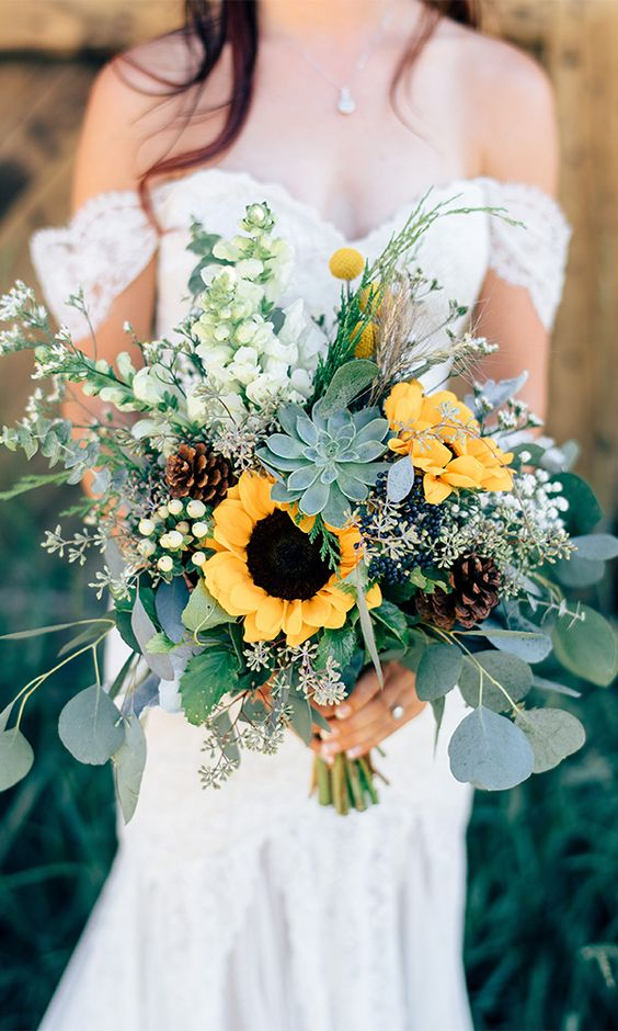 a creative summer wedding bouquet with woodland and farmhouse touches - with succulents, sunflowers, pinecones and billy balls is cool