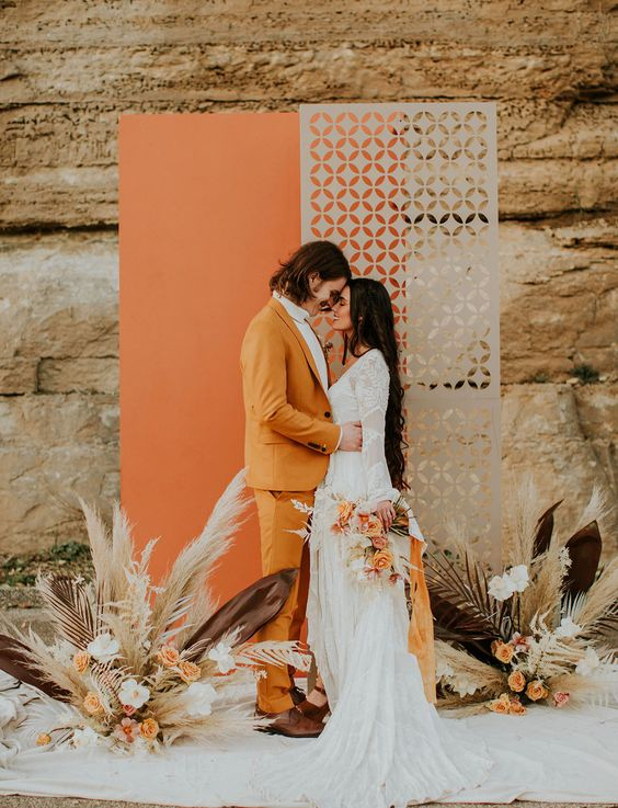 a creative wedding backdrop in orange and grey, with a laser cut part, floral arrangements and pampas grass can be a solution for a mid-century modern or 70s wedding