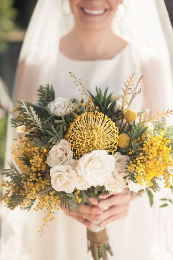 a creative wedding bouquet with white and yellow blooms, mimosa, billy balls and various types of greenery