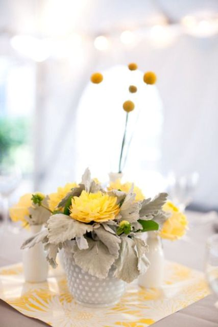 a creative wedding centerpiece of pale leaves, yellow blooms and billy balls is a pretty idea for a spring or summer wedding