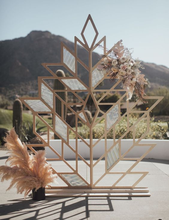 a creative wooden leaf wedding backdrop decorated with pastel adn neutral blooms, leaves and twigs and pampas grass is cool for a mid-century modern wedding