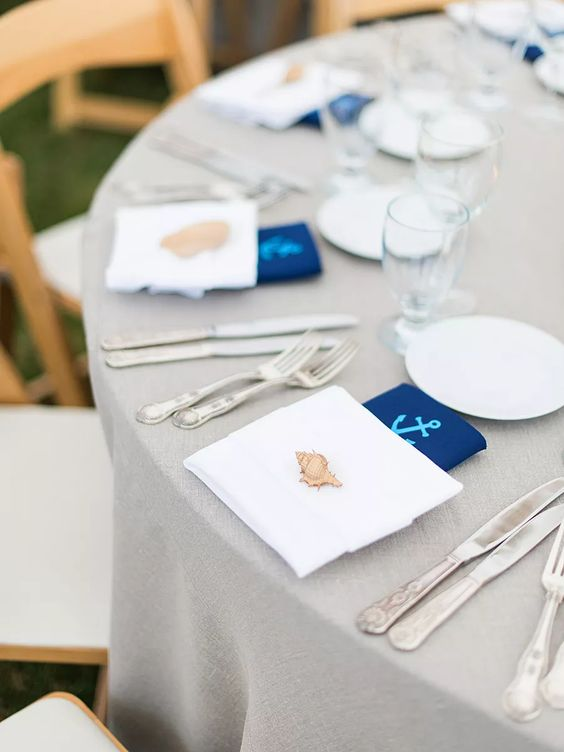 a cute nautical wedding tablescape with a grey tablecloth, white napkins, navy anchor ones, white porcelain is simple and lovely