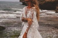 a dreamy celestial wedding dress with bell sleeves, an illusion neckline and stars all over the gown is just jaw-dropping