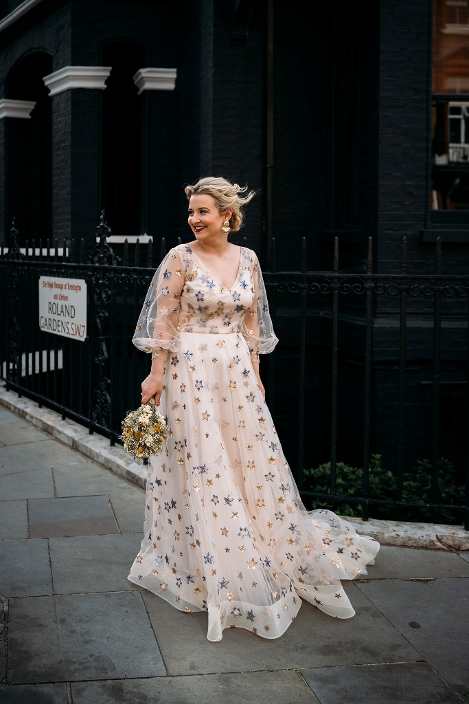 a fantastic blush A-line wedding dress with a V-neckline, puff illusion sleeves and foil stars all over the gown