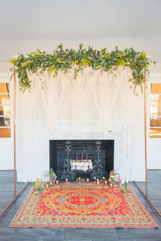 a fireplace and a copper weddng arch decorated with greenery, yellow blooms and candles on the bold rug for a bright mid-century modern wedding