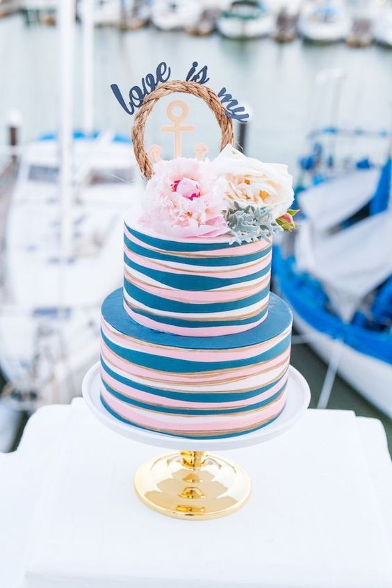 a funny and cheerful nautical wedding cake with white, pink and blue stripes, white and pink peonies and a rope piece with calligraphy
