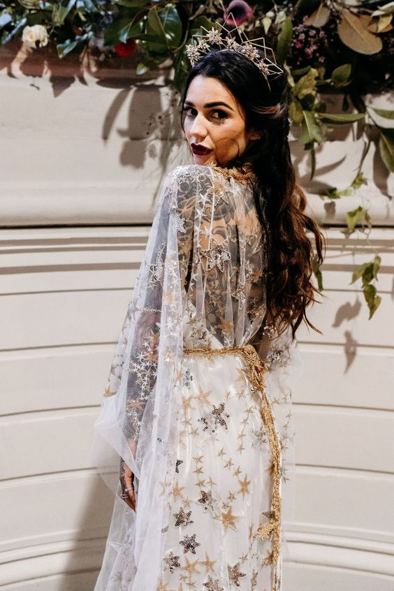 a gorgeous A-line wedding dress in white with gold and silver embroidered stars, an open back and a gold star sash plus a lovely crown