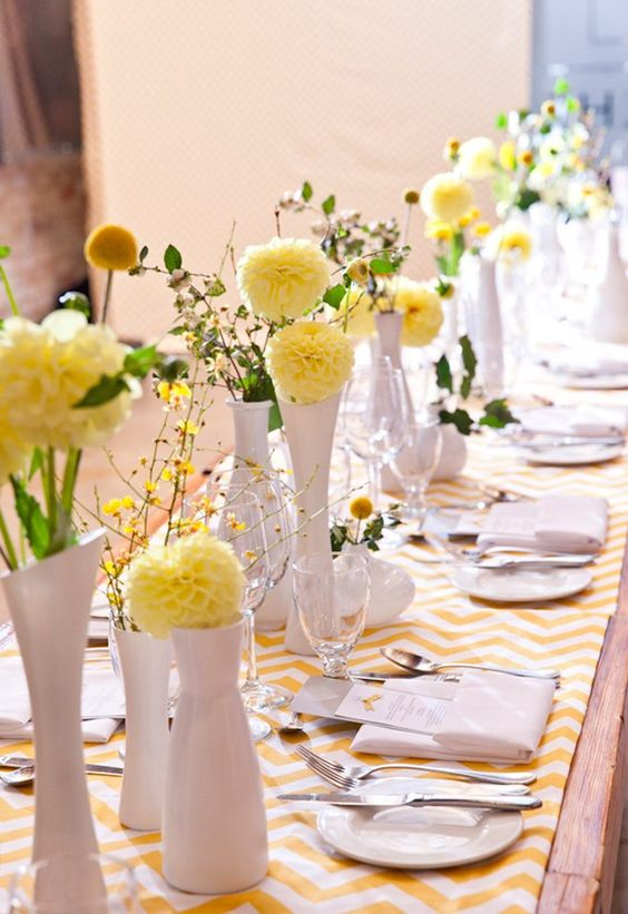 a gorgeous cluster wedding centerpiece of white vases, greenery, yellow dahlias and billy balls is amazing for spring