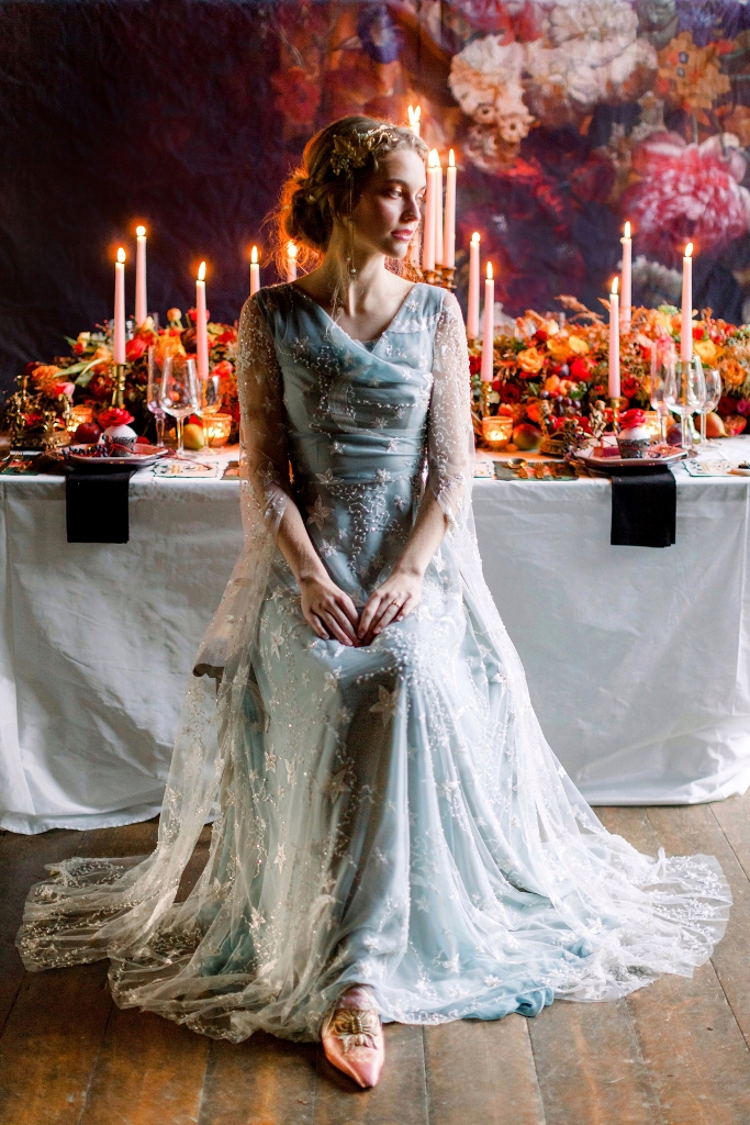 a gorgeous light blue celestial wedding dress with a draped bodice, bell sleeves and embroidered stars and moons is sparkling and chic