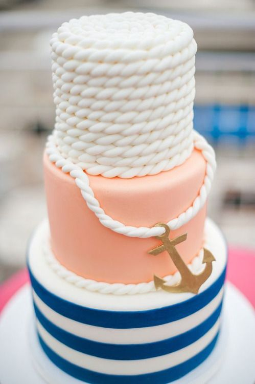 a gorgeous nautical wedding cake with a blue striped tier, a peachy one and a white rope one plus a gold anchor looks cheerful and fun