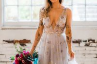 a grey A-line wedding dress with a plunnging neckline, thick straps and gold foil stars all over the dress
