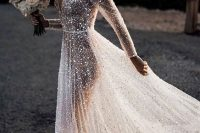 a jaw-dropping A-line silver sparkles wedding dress with a covered plunging neckline, long sleeves, see-through but with a nude underdress