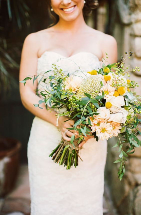 a large wedding bouquet with blush and neutral blooms, berries, billy balls and lots of greenery for a spring or summer wedding