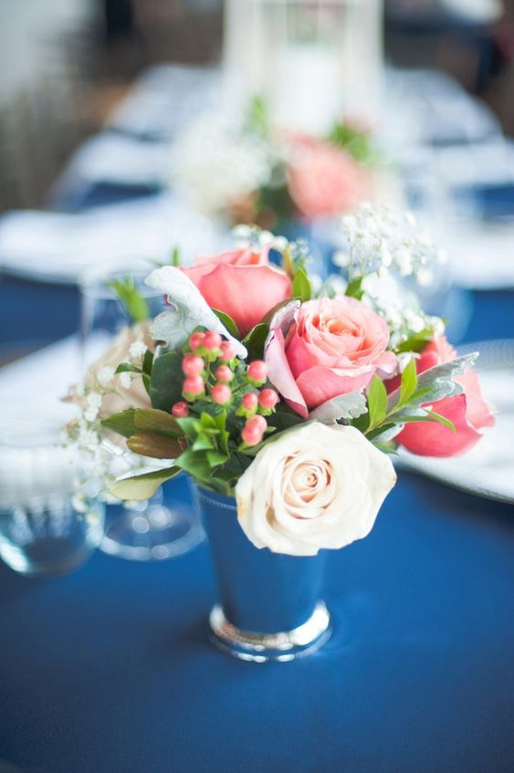 a lovely and easy nautical wedding centerpiece of a navy vase, white and pink roses and baby's breath plus berries is amazing
