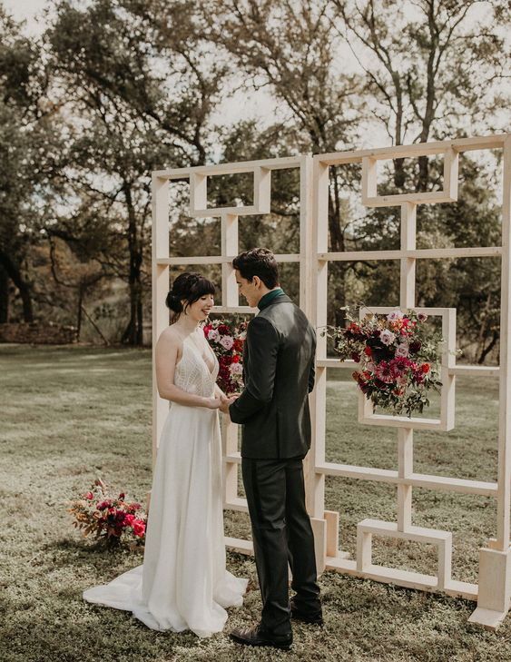 a lovely and simple white mid-century modern wedding backdrop decorated with greenery and pink and red blooms is a lovely idea