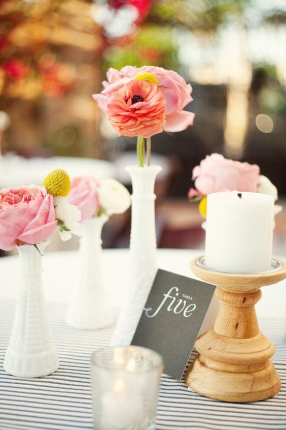 a lovely cluster wedding centerpiece of pink peonies, billy balls and white blooms in white vases plus a wooden candleholder