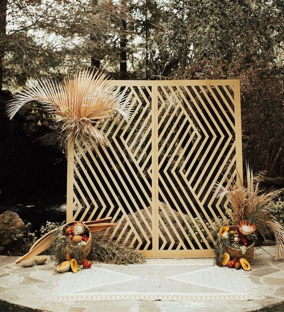 a lovely laser cut wedding backdrop of wood decorated with dried fronds, king proteas, fresh fruits and grasses for a mid-century modern tropical wedding