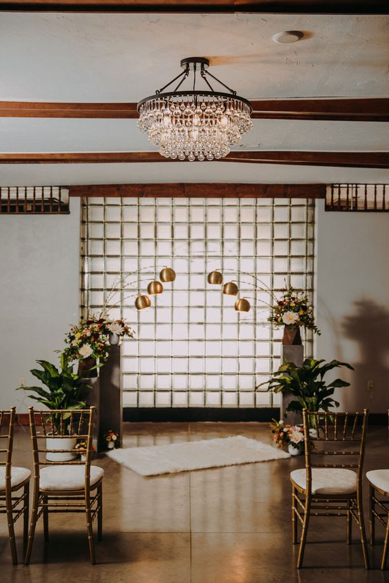 a lovely mid-century modern wedding backdrop of glass, with brass lamps and floral arrangements around is a stylish idea