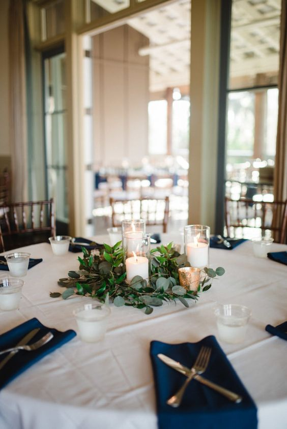 a lovely modern nautical wedding tablescape with a white tablecloth and navy napkins, candles with greenery for a centerpiece