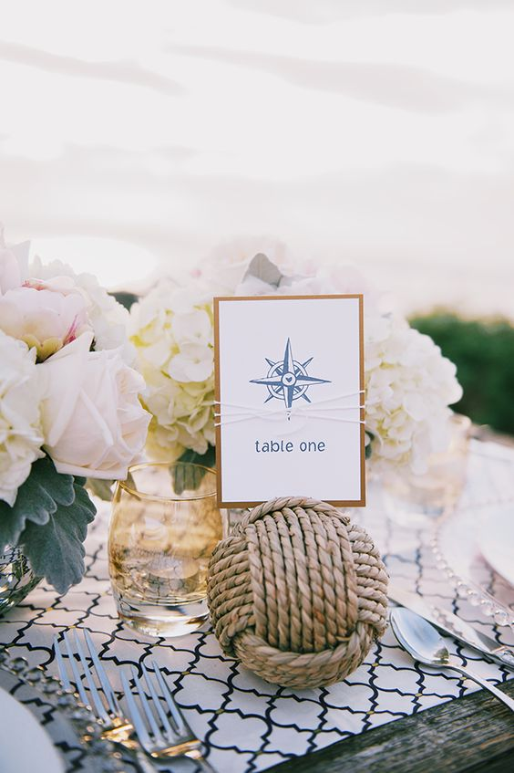 a lovely nautical wedding centerpiece of white and blush blooms, a rope ball with a table number