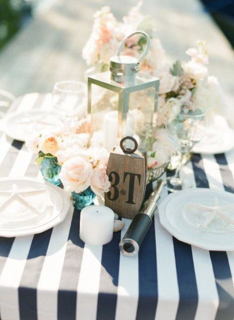 a lovely nautical wedding tablescape with a striped tablecloth, white plates and candles, blush blooms in turquoise vases and a candle lantern