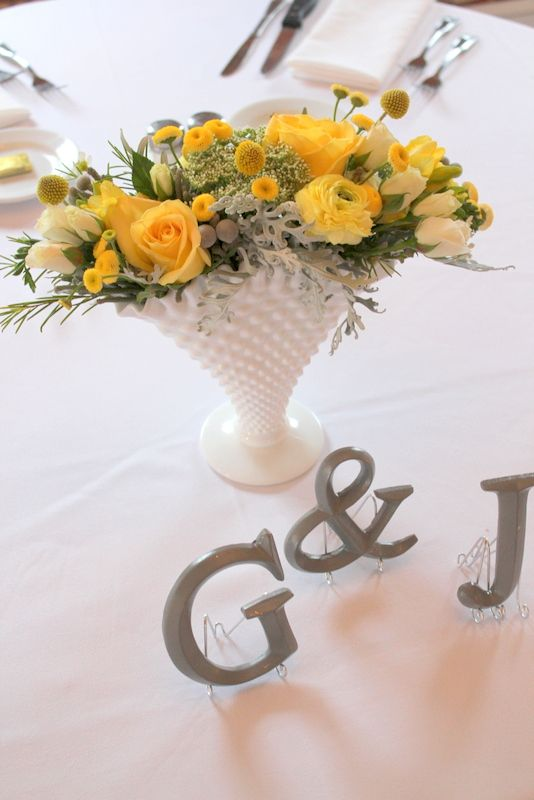 a lovely summer wedding centerpiece of yellow and white blooms, billy balls and greenery in a chic white vase