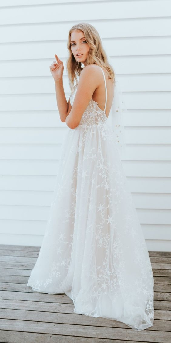a lovely wedding ballgown with spaghetti straps and star appliques all over the dress plus an open back is an amazing idea