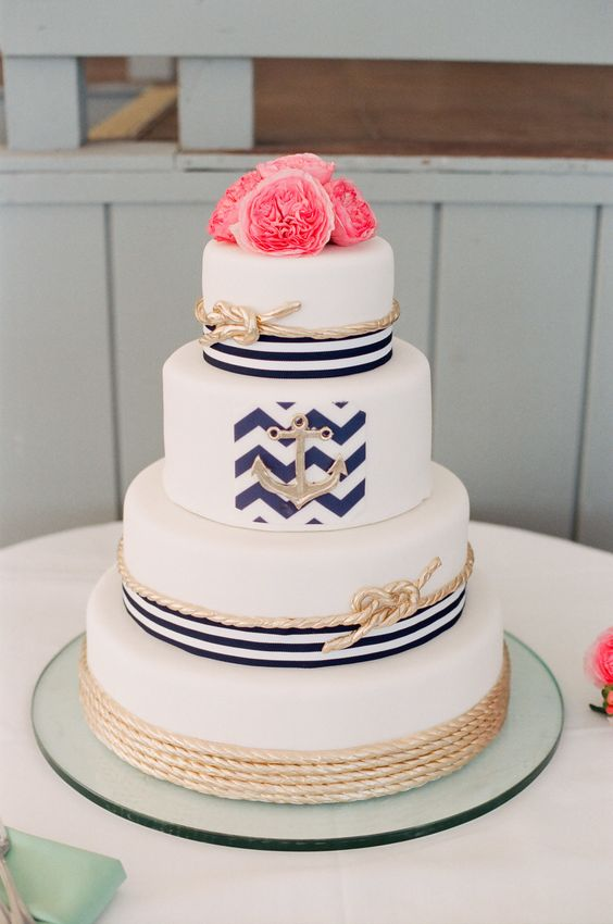 a lovely wedding cake with navy stripes, gold ropes and coral peonies on top is a fun and bold idea for a seaside wedding