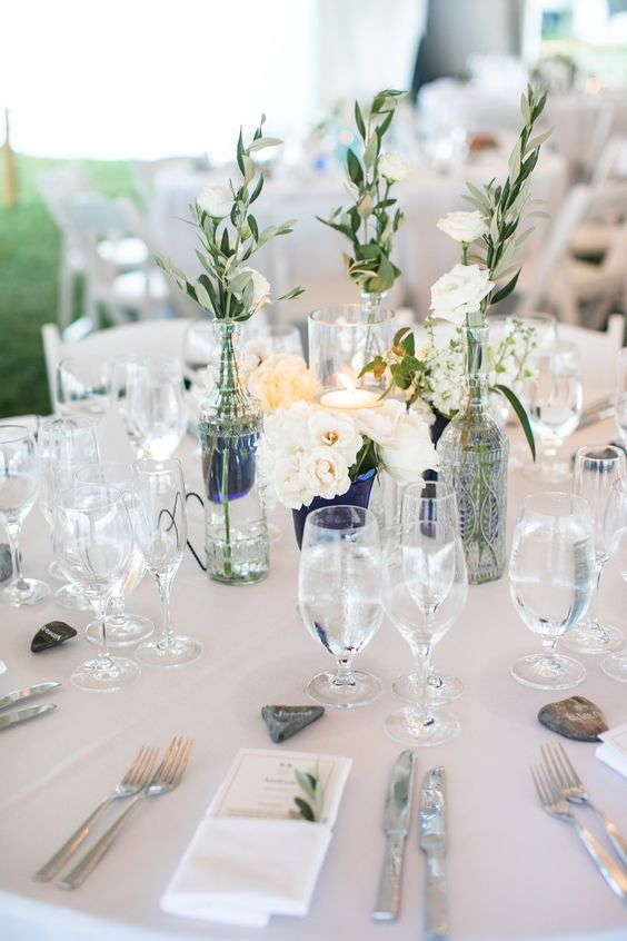 a lovely wedding tablescape with white linens, neutral blooms and a candle, pebbles and greenery, navy vases for a nautical wedding