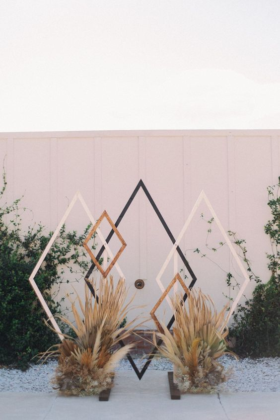 a mid-century modern and boho wedding backdrop of rhombs, pampas and other grasses is a lovely and pretty idea for a boho wedding