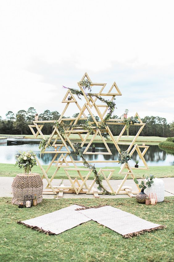 a mid-century modern wedding backdrop composed of many wooden triangles decorated with greenery, with wicker ottomans, greenery and candles and a view of the lake