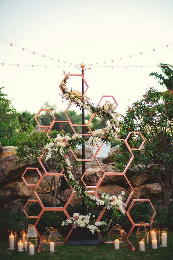 a mid-century modern wedding backdrop of honeycombs, with greenery and neutral blooms and candle lanterns on the ground
