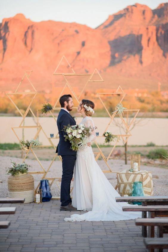 a mid-century modern wedding backdrop of triangles, a printed ottoman, potted greenery and air plants, candle lanterns and a gorgeous mountain view