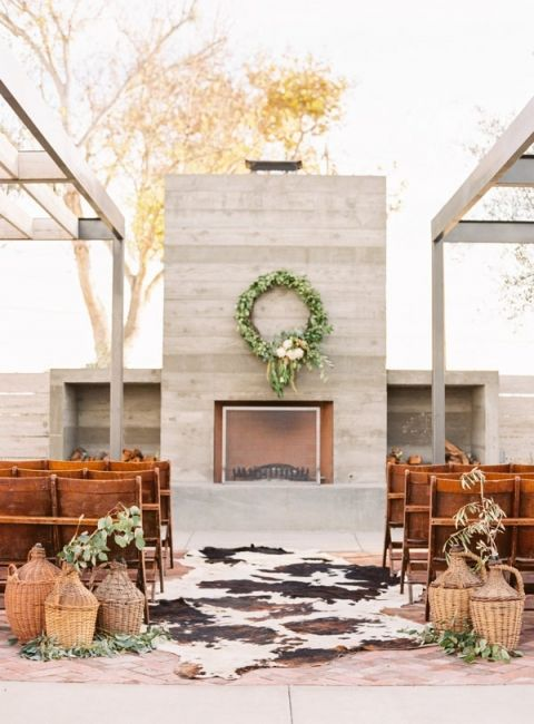 a mid-century modern wedding space with a fireplace, a greenery wreath, animal skins, greenery and woven bottles is cool