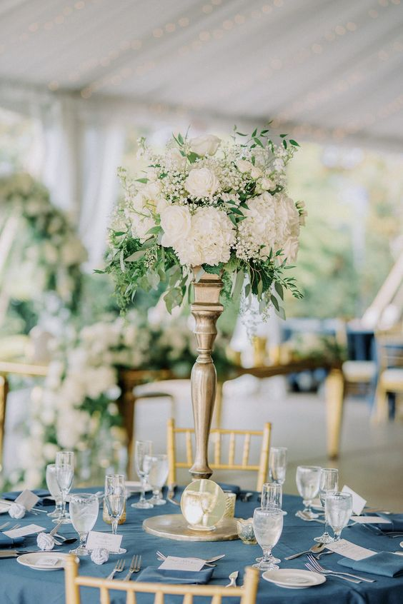 a modern nautical wedding tablescape with a blue tablecloth, a white tall floral centerpiece with greenery and white menus