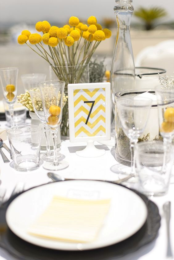 a modern wedding centerpiece of billy balls in a clear vase, with a chevron table number and some yellow baby's breath for addition