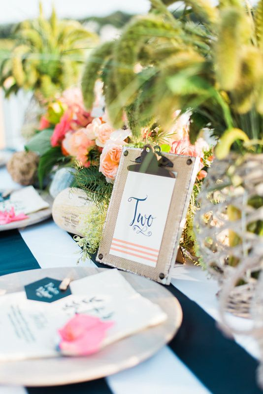 a nautical tropical wedding tablescape with a striped tablecloth, wooden chargers, bright blooms and greenery, pebbles and driftwood