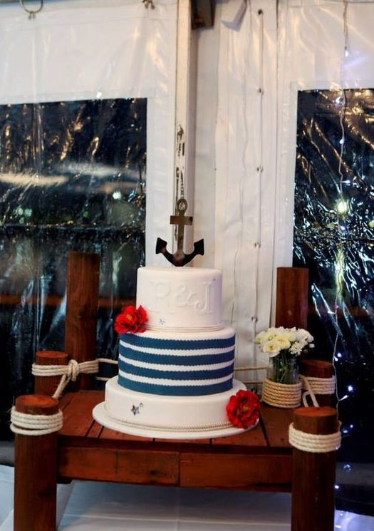 a nautical wedding cake in white and blue, with stripes, monograms, red blooms and an anchor on top is a stylish idea for a lovely wedding