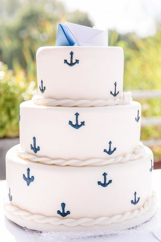 a nautical wedding cake in white with navy anchors, ropes, paper boat toppers for a touch of casual and fun