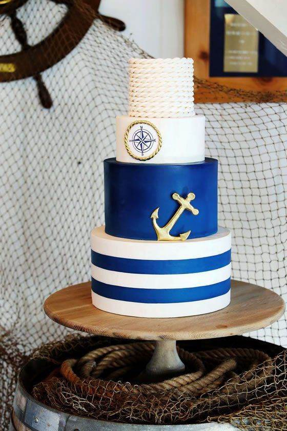 a nautical wedding cake with a striped, a bold blue and a compass tier, a rope tier and an anchor is a stylish and bold idea to rock