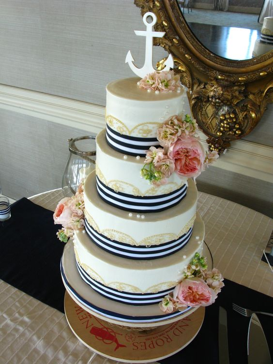 a nautical wedding cake with gold lace, navy ribbons, pink blooms and greenery and an anchor on top