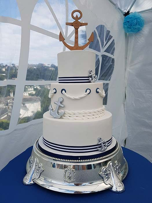a nautical wedding cake with navy and white stripes, rope, anchor decor is an amazing and very cheerful nautical idea to try