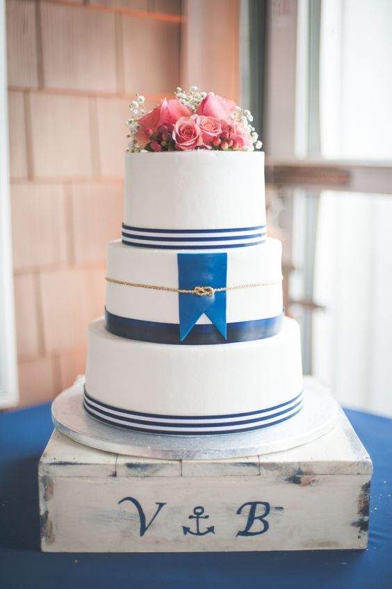 a nautical wedding cake with navy stripes, a navy flag, a gold roper, pink blooms and baby's breath is a gorgeous idea