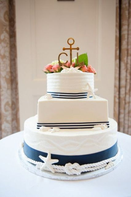 a nautical wedding cake with white and navy tiers, rope and starfish, with peachy blooms and greenery and an anchor