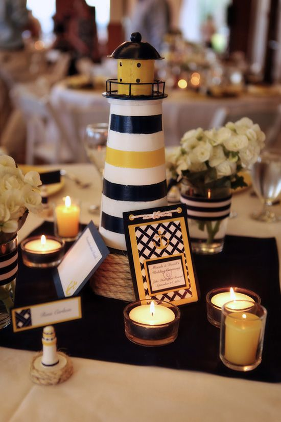 a nautical wedding centerpiece of a beacon, lots of candles and a bright table number is a gorgeous idea