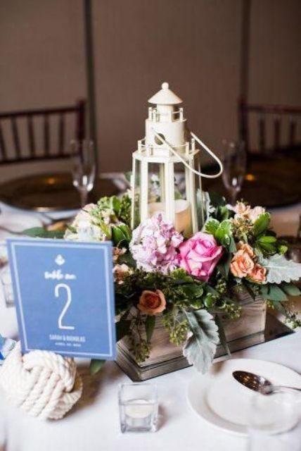 a nautical wedding centerpiece of a wooden box with pink blooms and greenery, a candle lantern shaped as a beacon, a rope knot with a table number