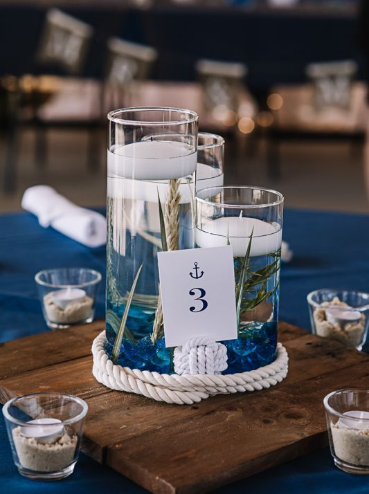 a nautical wedding centerpiece of a wooden plaque, rope and floating candles plus a table number is gorgeous
