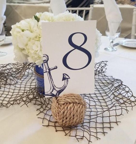 a nautical wedding centerpiece of net, a rope ball, white hydrangeas in a navy vase and a table number wiht an anchor